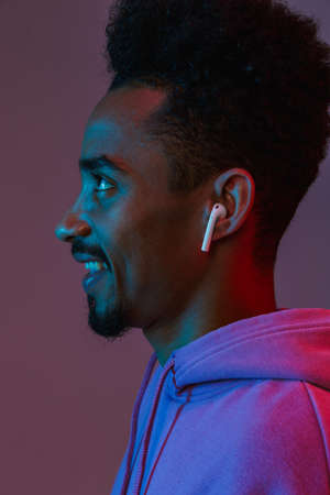 Portrait in profile of smiling african american man in colorful hoodie listening to music with earpod isolated over violet background 免版税图像