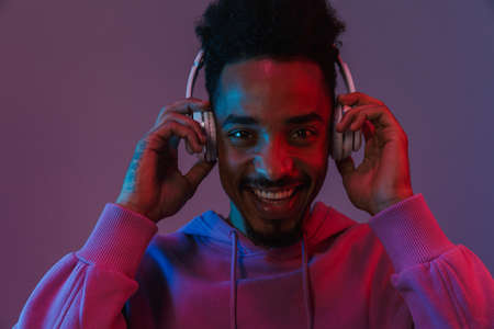 Portrait of laughing african american man in colorful hoodie listening to music with headphones isolated over violet background