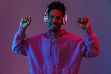 Portrait of excited african american man in colorful hoodie listening to music with headphones isolated over violet background 免版税图像
