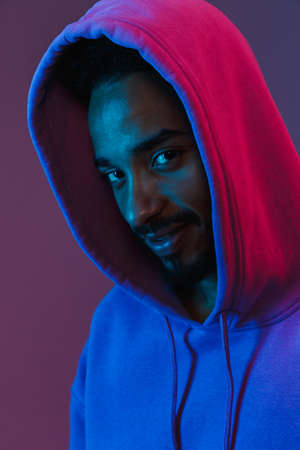 Portrait of smiling african american man in colorful hoodie posing and looking at camera isolated over violet background