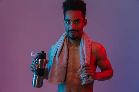 Portrait of young shirtless african american man poising with thermos bottle and towel isolated over violet background