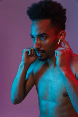 Portrait of bearded shirtless african american man poising with earpod isolated over violet background Imagens