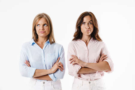 Image of displeased beautiful two women posing with hands crossed on camera isolated over white background