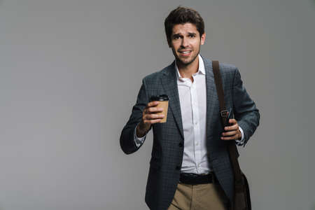 Photo of smiling confident businessman drinking coffee takeaway and using cellphone isolated over grey wall Stock Photo