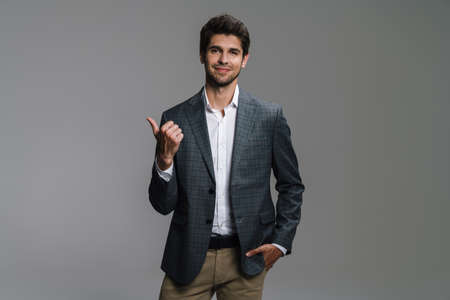 Photo of cheerful businessman in jacket smiling and pointing finger aside isolated over grey wall
