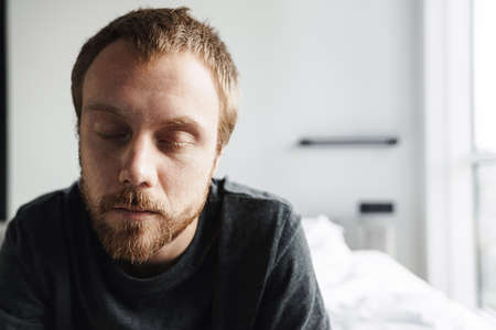 Photo closeup of sleepy redhead man posing with eyes closed while sitting on bed at bright room