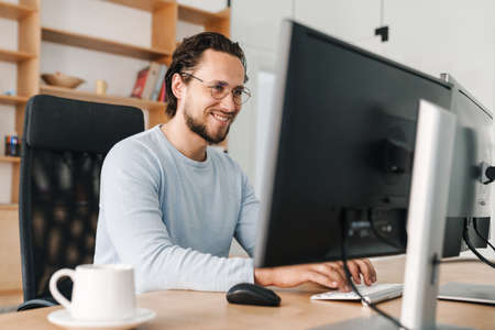 Image of smiling unshaven programmer man wearing eyeglasses working with computer in office Stock Photo