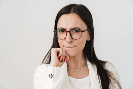 Photo of displeased businesswoman in eyeglasses looking at camera isolated over white background