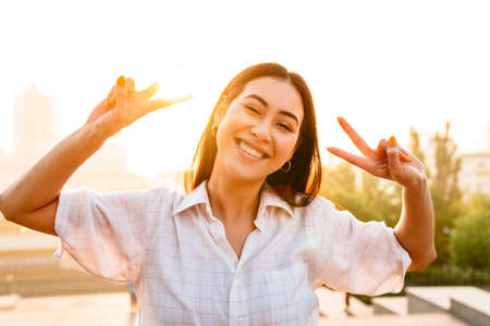 Photo of joyful beautiful asian woman laughing and gesturing peace sign while walking outdoors