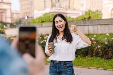 Image of joyful couple taking photo on cellphone and showing thumb up while walking on boulevard