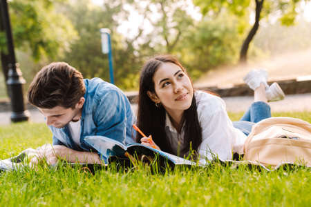 Image of joyful multicultural student couple doing homework and smiling while lying on grass in park