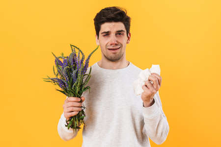 Photo of handsome unhappy man with allergy posing with flowers isolated over yellow background