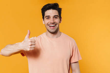 Photo of happy handsome man showing thumb up and smiling isolated over yellow background Banco de Imagens
