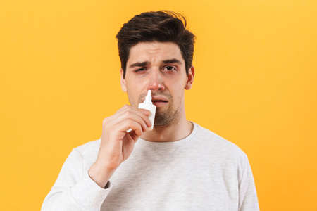 Photo of handsome unhappy man with allergy using nose drops isolated over yellow background 免版税图像