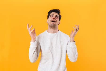 Photo of sick unhappy man in casual wear looking upward and crying isolated over yellow background
