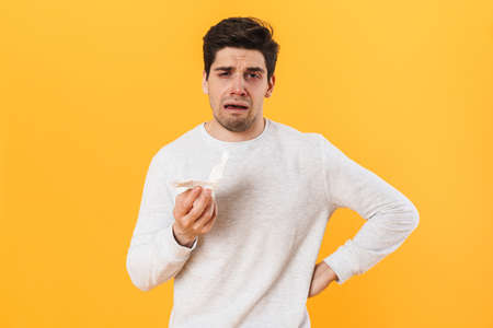 Photo of sick unhappy man with runny nose posing with tissue on camera isolated over yellow background
