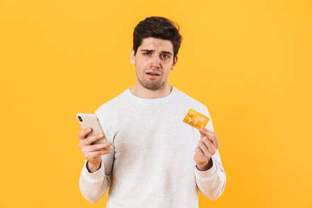 Photo of handsome sick man holding credit card and smartphone isolated over yellow background 免版税图像