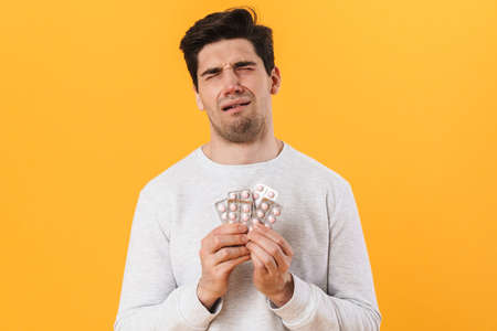 Photo of bristle unhappy man with allergy posing with medicine and crying isolated over yellow background 免版税图像