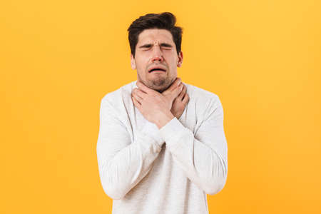 Photo of sick unhappy man having painful sore throat and touching neck isolated over yellow background