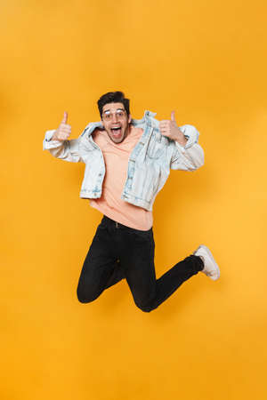 Photo of delighted handsome man jumping and showing thumb up isolated over yellow background