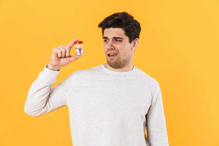Photo of handsome unhappy man with allergy posing with medicine isolated over yellow background