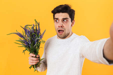 Photo of scared man with allergy taking selfie photo while holding flowers isolated over yellow background 免版税图像