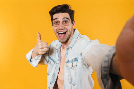 Photo of delighted bristle man showing thumb up while taking selfie photo isolated over yellow background