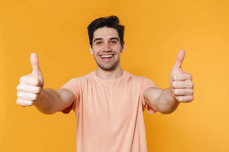Photo of happy handsome man showing thumbs up and smiling isolated over yellow background