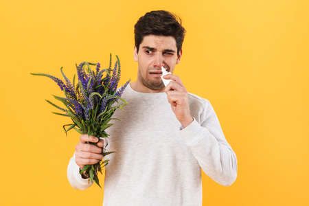 Photo of unhappy man with allergy using nose drops while holding flowers isolated over yellow background
