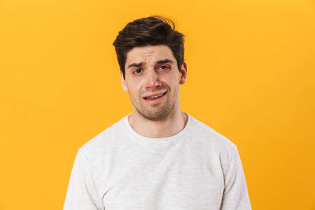 Photo of unhappy bristle man in basic t-shirt posing and looking on camera isolated over yellow background