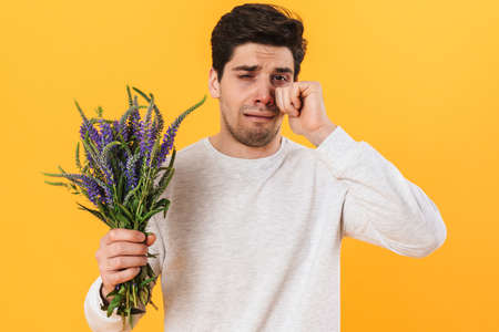 Photo of handsome unhappy man with allergy crying and posing with flowers isolated over yellow background