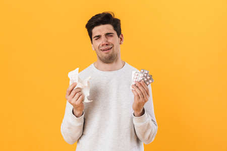 Photo of bristle unhappy man with allergy posing with pills and napkin isolated over yellow background