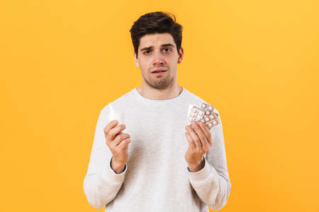 Photo of bristle unhappy man with allergy posing with pills and nose drops isolated over yellow background