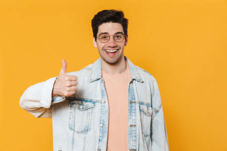 Photo of joyful young man in eyeglasses smiling and showing thumb up isolated over yellow background Banco de Imagens