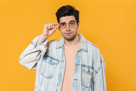 Photo of confused young man in eyeglasses posing and looking at camera isolated over yellow background