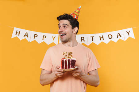 Photo of excited caucasian man in party cone holding birthday cake and smiling isolated over yellow background Standard-Bild
