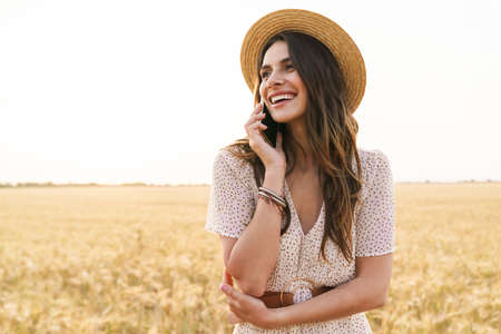Photo of laughing nice woman in straw hat talking on cellphone while walking on wheat field at summer day