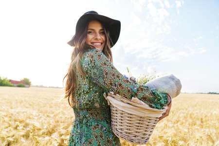 Photo of happy young woman wearing stylish hat smiling while walking with basket at picnic on wheat field