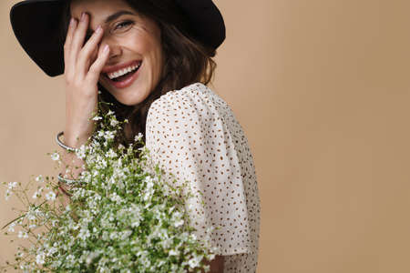 Photo of cheerful beautiful woman in hat laughing while posing with flowers isolated over beige background Foto de archivo