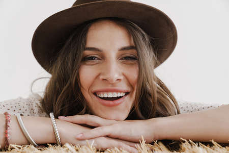 Photo of happy seductive woman in hat laughing while leaning on hay isolated over white background