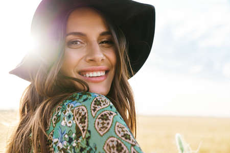 Photo closeup of cheerful young woman wearing stylish hat smiling while walking at picnic on wheat field Foto de archivo