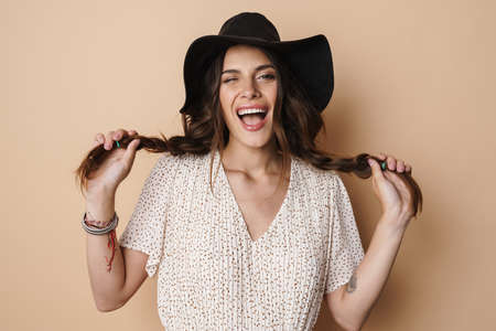 Photo of excited beautiful woman in hat winking and making fun with pigtails isolated over beige background