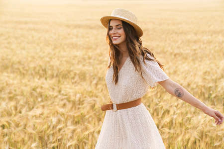 Photo of beautiful happy woman in straw hat smiling and walking on wheat field at summer day