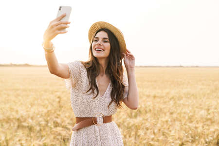 Photo of laughing nice woman talking selfie photo on cellphone while walking on wheat field at summer day