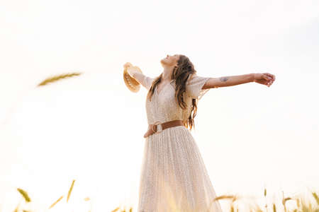 Photo of beautiful happy woman with straw hat smiling and dancing on wheat field at summer day