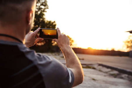 Image from back of sportsman taking photo on mobile phone while working out on sunrise outdoors Stock fotó