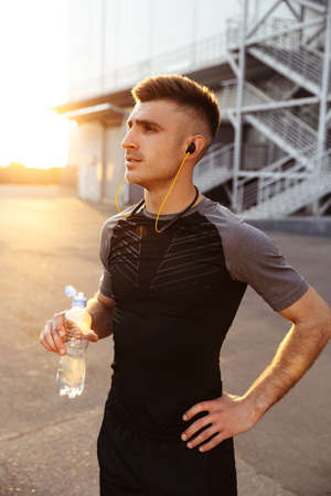Image of young athletic sportsman in earphones drinking water while working out at urban area outdoors