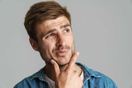 Portrait of redhead puzzled man posing and thinking at camera isolated over grey background Imagens