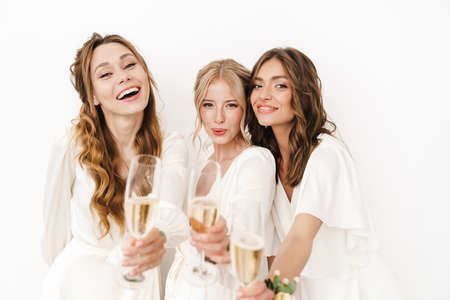 Photo of joyful beautiful bridesmaids laughing and drinking champagne isolated over white wall