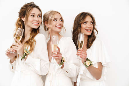 Photo of joyful beautiful bridesmaids smiling and drinking champagne isolated over white wall